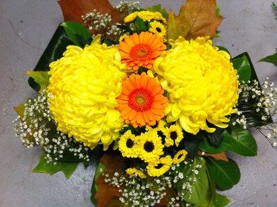 Bloemstuk bolchrysant gele en oranje tinten