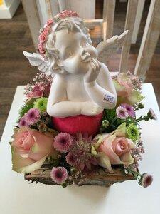 Bloemstukje in schorsbakje roze en groene tinten met engeltje