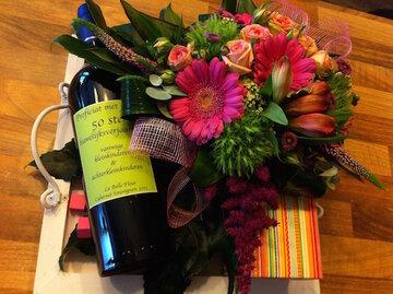 bloemstuk met fles wijn en pralines