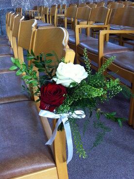 Stoeldecoratie kerk 1 rode en 1 witte roos met groensoorten